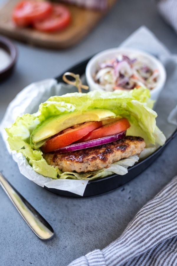 Keto, paleo, gluten-free turkey burgers wrapped in lettuce with tomato and avocado