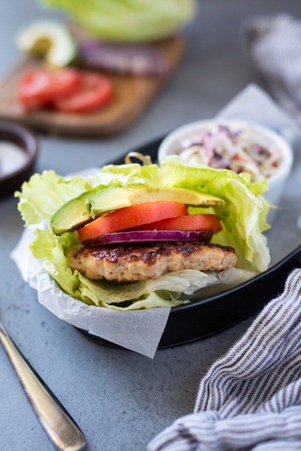 front view of grilled turkey burgers with lettuce wrap, tomato and avocado
