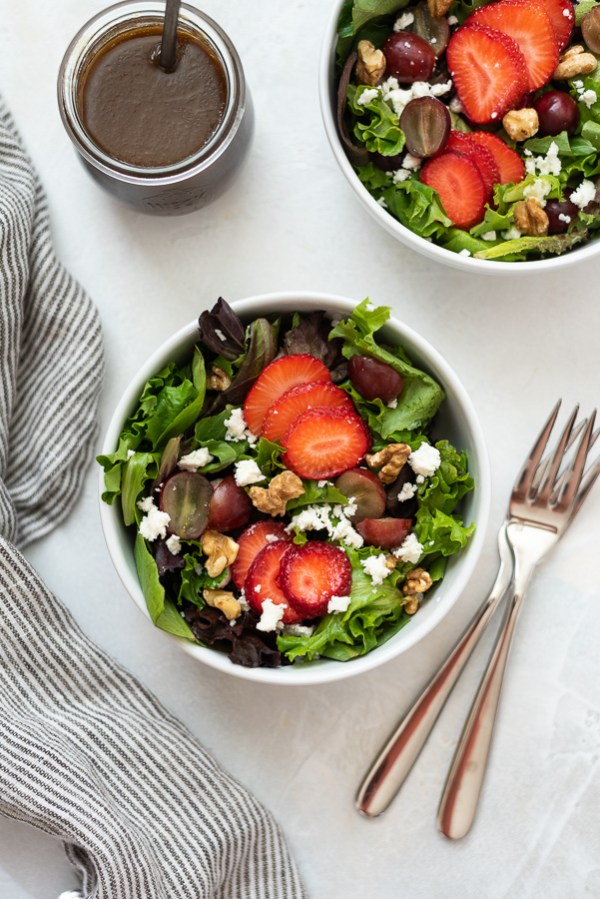 overhead shot of strawberry salad in white bowl
