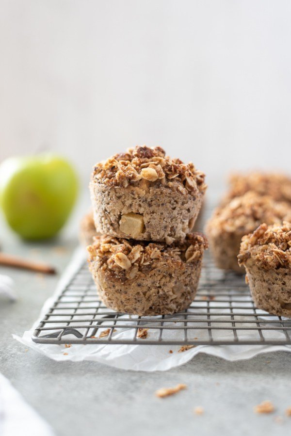 apple crisp baked oatmeal cups stacked up on a wire rack