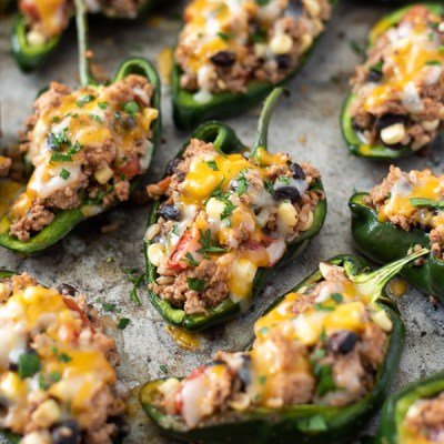 front view of stuffed poblano peppers on a sheet pan with melted cheese