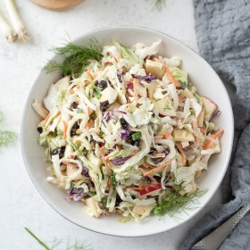 overhead shot of bowl of creamy no mayo coleslaw with gray linen