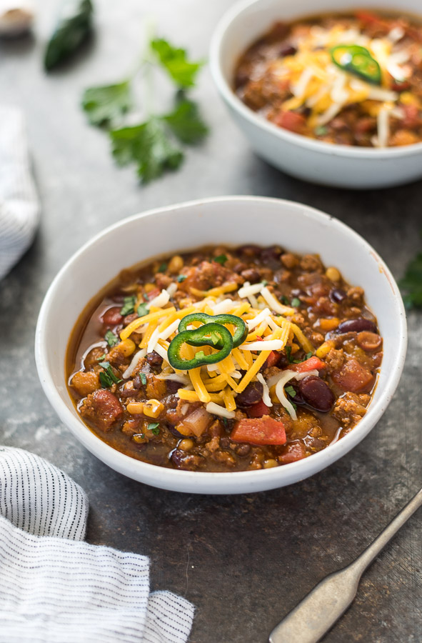 pumpkin chili in white bowl with cheese on top