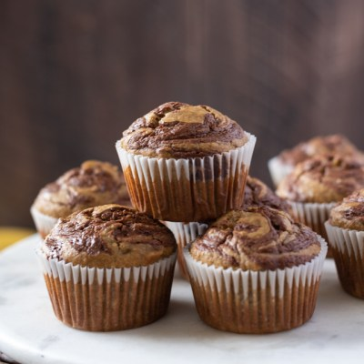 Nutella Banana Swirl Muffins stacked up on a marble server