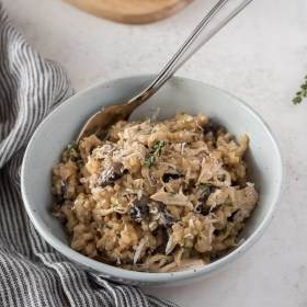 close up of instant pot chicken and rice in a bowl with sprig of thyme on top