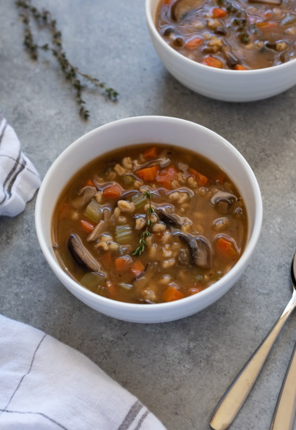 mushroom barley soup in bowl with spoon alongside