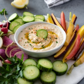 white bean hummus on a serving platter surrounded by fresh vegetables