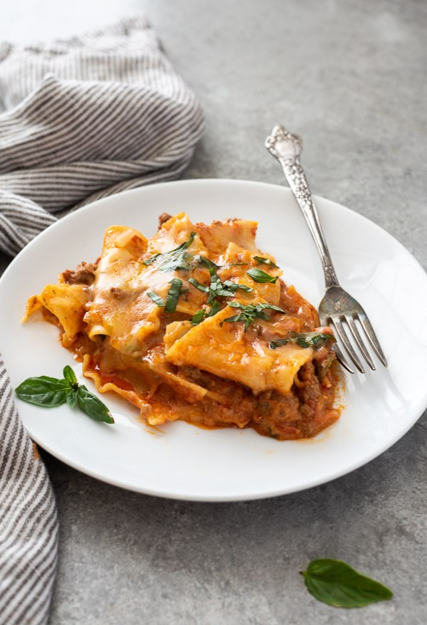 serving of skillet lasagna on plate with basil on top and alongside