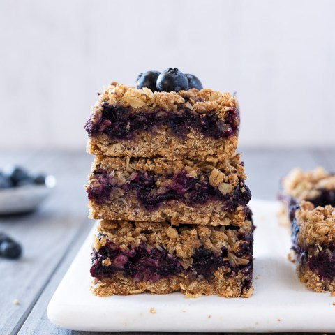 blueberry crumble bars stacked up with blueberries on top