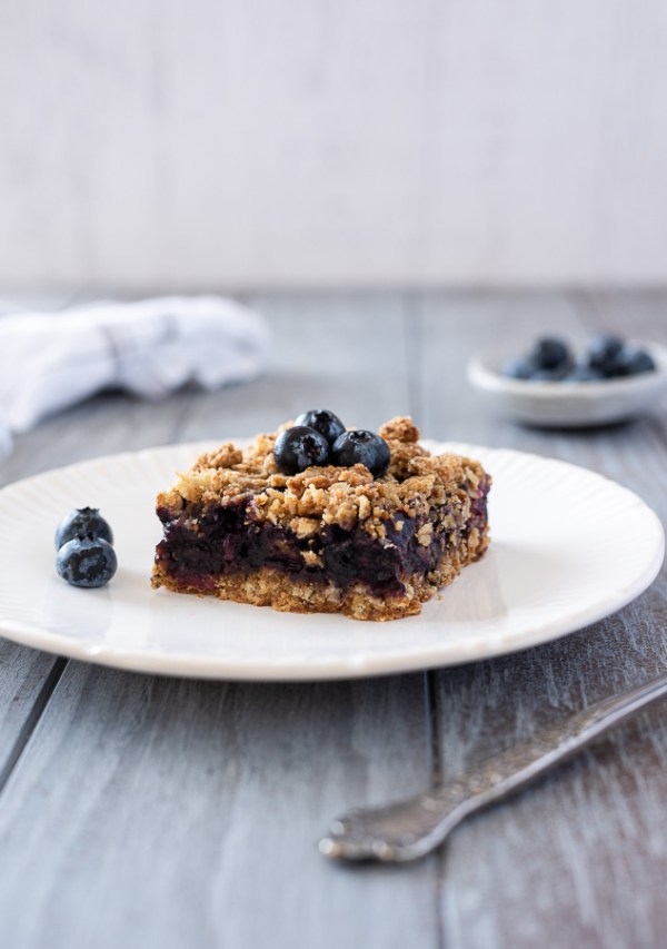 blueberry crumble bar on a plate with blueberries on top and fork alongside