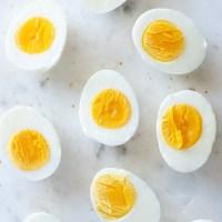 hard boiled eggs cut in half on a marble board