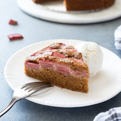 slice of rhubarb cake on a plate with vanilla ice cream