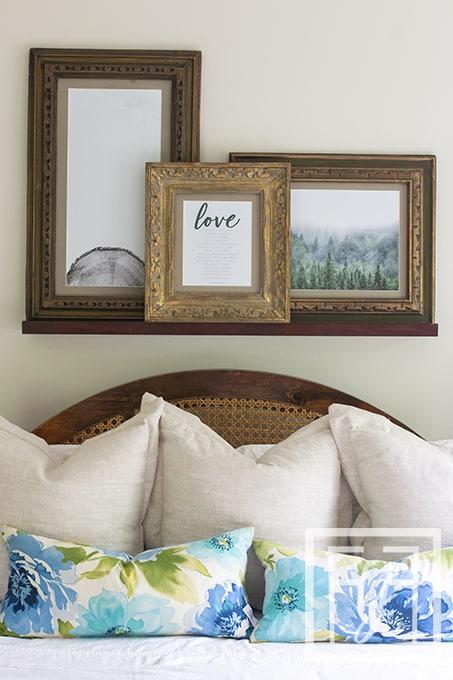 vintage frames on photo ledge over king size bed