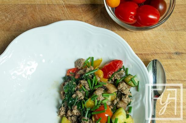 summer vegetable and sausage hash in white bowl