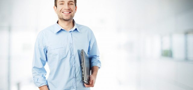 Handsome businessman with laptop standing