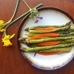 Balsamic Roasted Asparagus and Carrots on a plate surrounded by yellow and purple flowers