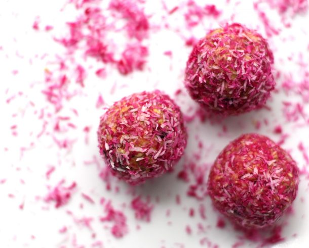 Naturally Pink Protein Snacks with naturally pink coconut flakes scattered around. The perfect gluten-free snack for kids!