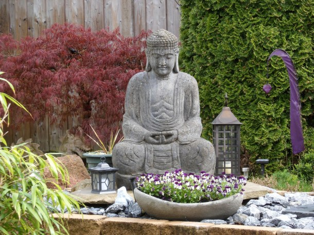Large Buddha statue surrounded by flowers, plants, and trees in a meditation garden