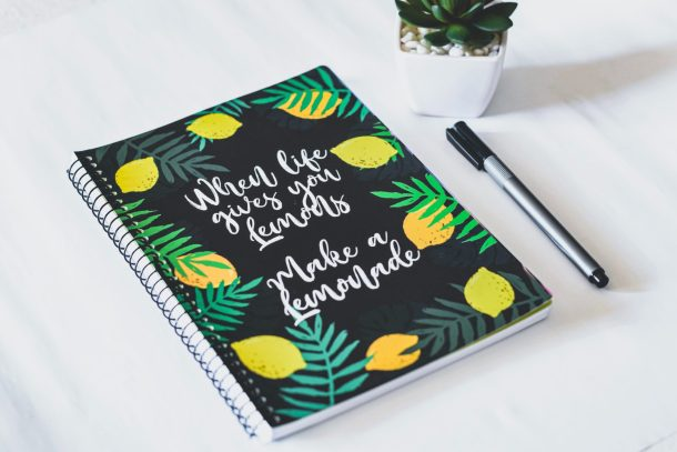 "This is an example of a meditation journal. It's a black notebook with green lemons and leaves around the border. The text reads ""When live gives you lemons, make a lemonade"" in white letters on top of the notebook."