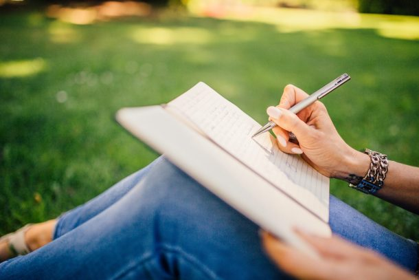A woman writing in a meditation journal with grass in the background