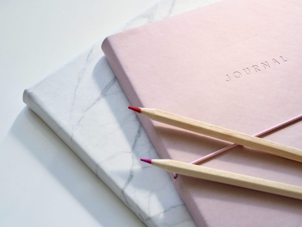 A pink journal and a white journal with two red pencils sitting on a countertop