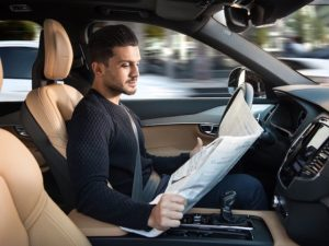 Driver reading newspaper at wheel of driverless Volvo