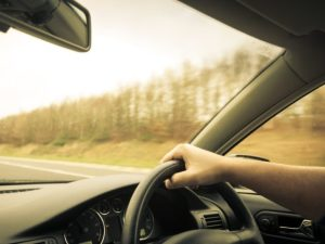 Image of man's arm holding steering wheel driving on road