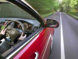 Man driving on country road in red car