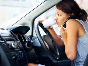 Businesswoman multitasking while driving, drinking coffee and talking on the phone-distractions