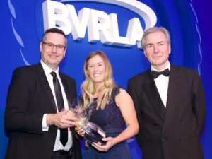 Alphabet's Hannah Broad receiving her award from Owen Gregory, director fleet operations at Ford Motor Company, with BVRLA chief executive, Gerry Keaney (right).