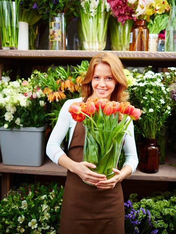 fleuriste dans sa boutique avec un vase de tulipe dans les mains