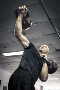 a strong man lifts kettle bells