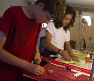 Bryce and Lion cutting out material for puppets' costumes.