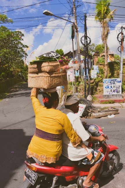 Balinese couple on a motorbike, woman carrying offerings on her head, Galungan 2014