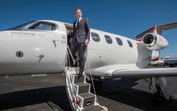 Alex Wilcox, the chief executive officer and founder of JetSuite, stands in the doorway of the company's Phenom 100 jet at John Wayne Airport.