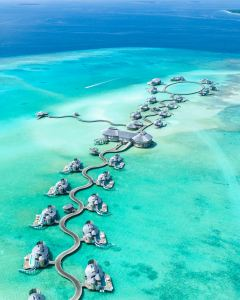 Overwater bungalow hotel in Maldives with green water