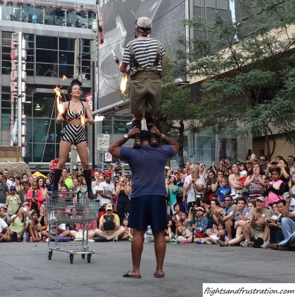 Let us juggle fire whilst stood on a shopping trolley or the shoulders of a guy at Buskerfest Toronto (4)
