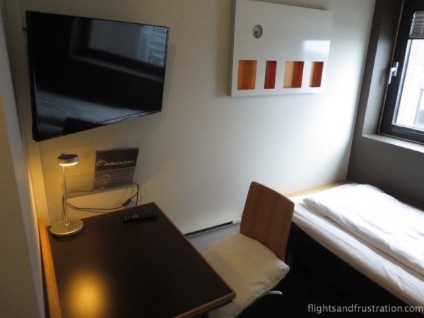 Flat screen tv, desk, chair and bed beside the window - is this where to stay in norway