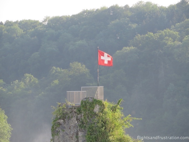 A Swiss flag sits proudly on top of the rock inbetween the Rhine Falls