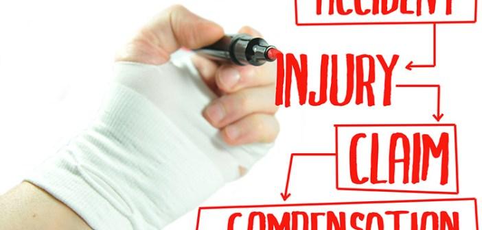Injured hand writing injury claim procedure on screen