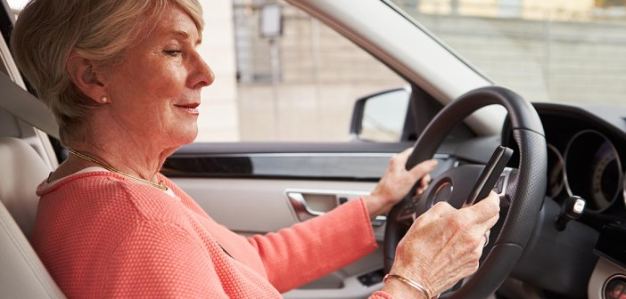 In car view of senior female driver texting using smartphone