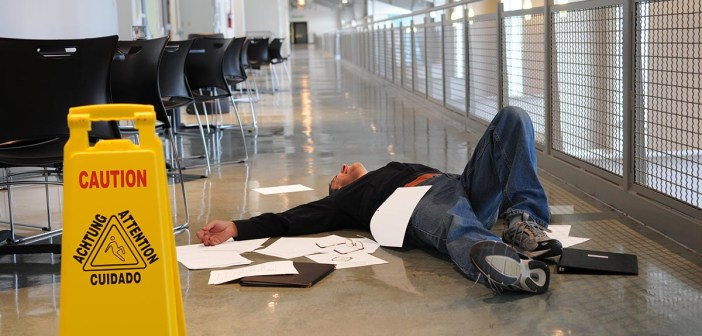Man lies on the wet floor on which he slipped in spite of caution sign