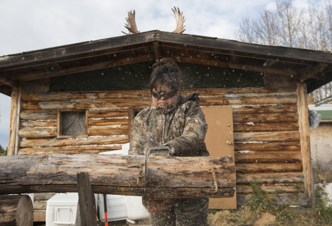 Anita Chicot cuts wood for the fire. Everyone is expected to pitch in and help with camp duties during the harvest.