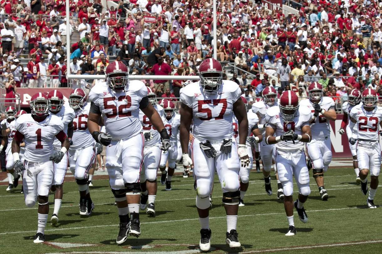 A college football team entering the field of play