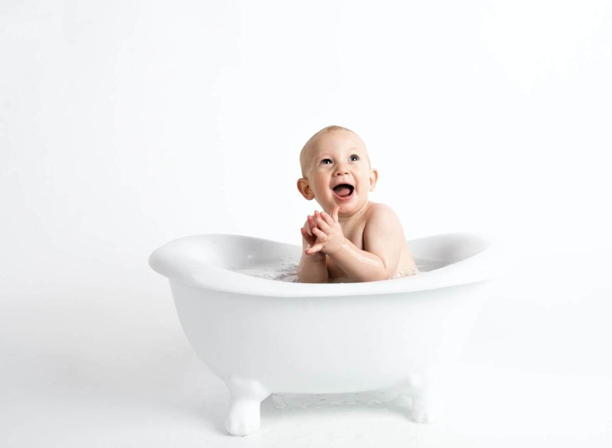 Happy baby inside white bathtub with water