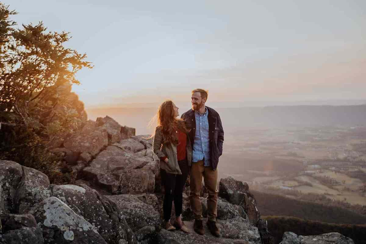 A couple stands on a huge rock in Shenandoah National Park while the sun sets behind them.