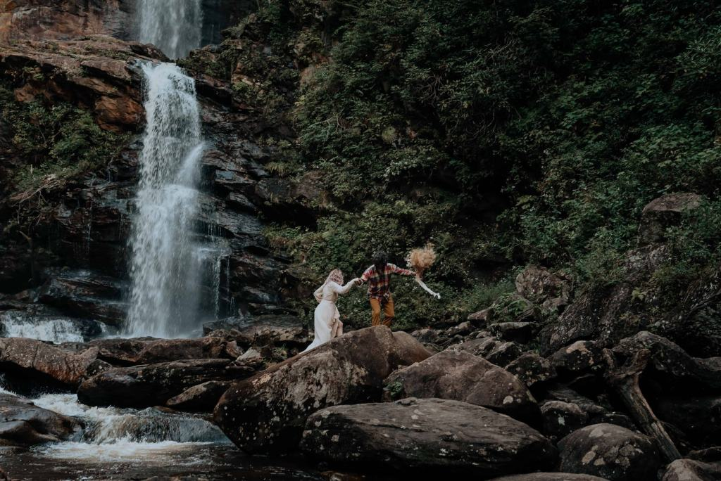 A newly-eloped couple scrambles across some large rocks at the base of an epic waterfall