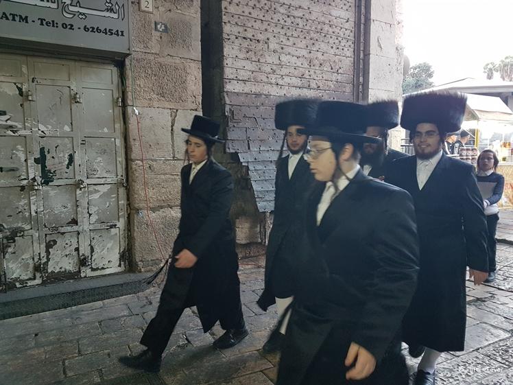 Jewish Orthodox men walking inside Damascus Gate on their way to Western Wall for Shabbat prayers Jerusalem