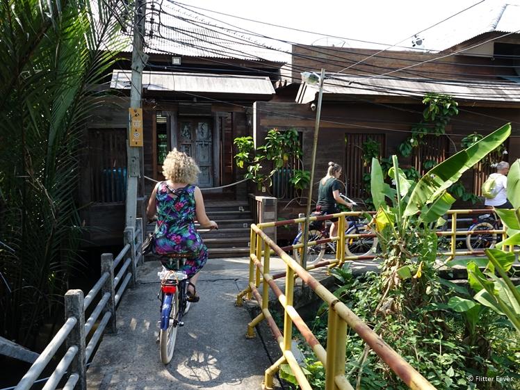 Cycling along teak wooden houses on Bang Kachao island Bangkok
