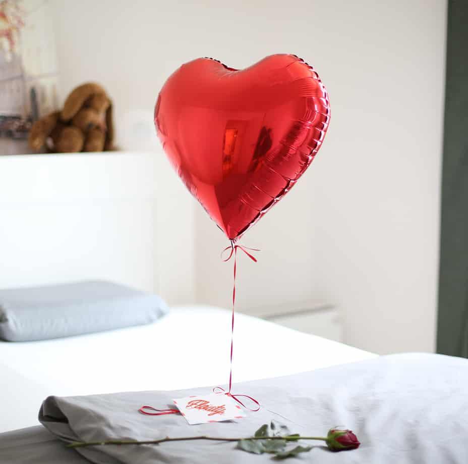 Roter Floatyballon auf dem Bett mit einer Rose
